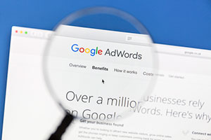 Magnifying glass looking over the benefits of paid ads vs organic seo