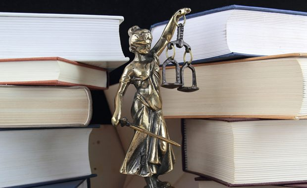 law and justice symbol set in front of a stack of law books to resemble a law firm that benefits from digital marketing services