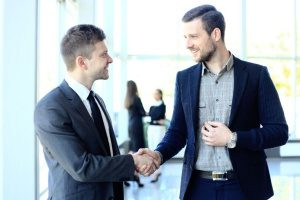 handshake between the owner of a digital marketing agency and an attorney who are going to discuss a strategic law firm content marketing plan