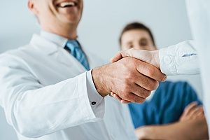 a handshake between a dentist and the CEO of a dental marketing agency after a successful meeting about SEO techniques