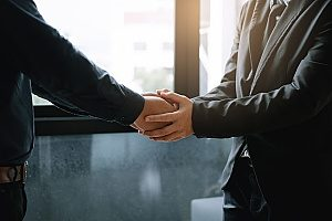 a new client of a law firm shaking hands with the firms main attorney who found the firm with the help of a digital marketing agency