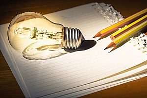 a shining lightbulb and pencils on top of lined paper symbolizing the creation of content for law firms which is a good content marketing strategy