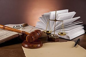 a gavel and balance next to a law book that is all owned by an attorney who has seen a drastic increase in his client book due to proper keyword research
