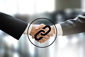 an SEO backlinking concept image showing two businessmen shaking hands with a chain link graphic over top of the handshake