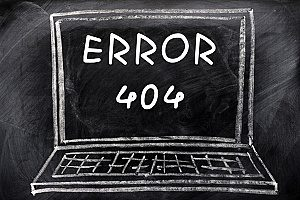 error 404 written in chalk along with a computer on a chalkboard to represent how SEO for dentists is useful in terms of fixing broken links