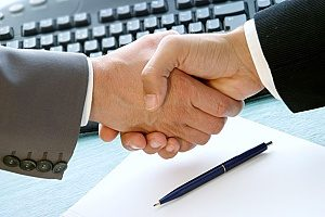 a dental marketing agency shaking hands with a dentist to agree on a dentist internet marketing services contract