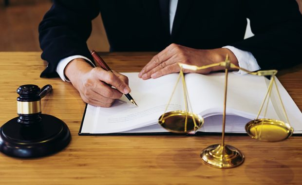 a hammer and gavel next to an attorney who is taking notes about law firm marketing strategies as he consults with a digital marketing agency