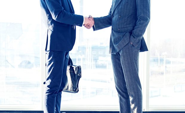 an attorney shaking hands with the owner of a digital marketing agency so they can develop a strategic law firm marketing plan