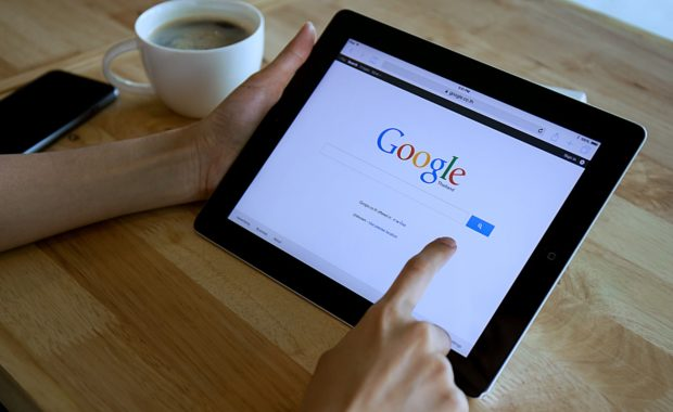 an individual using Google on his iPad to learn about search engine optimization vs search engine marketing and which would be better for his business