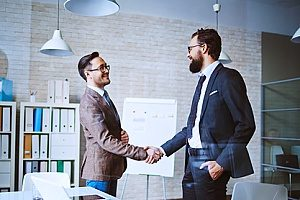 two business professionals shaking hands in order to close out an insurance marketing meeting