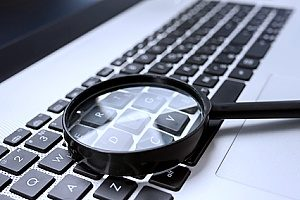 a magnifying glass placed on top of a keyboard to demonstrate the impact of dental SEO