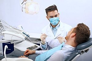 a male dentist helping out a patient with a cavity after the patient found his practice through dental internet marketing in a search engine results page