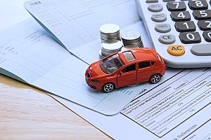 a model car next to coins and a calculator representing insurance agencies and how they can increase their book of clients through insurance marketing strategies