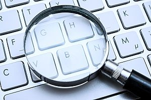 keyword research concept demonstrated by a magnifying glass over a keyboard to show how an insurance marketing agency can help any insurance company